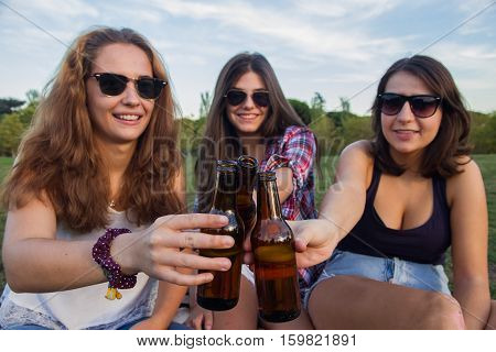 Girls enjoying. They are friends celebrating the holiday having a good time drinking beer in a park. They are toasting with bottles and they are wishing each other all goes very well. They're happy.