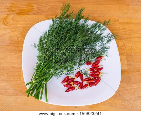 Close up branches of green fennel and red chili peppers on white plate, rustic wooden background, top view Raw organic fennel ready to cook. Fennel leaves and fennel stalk.