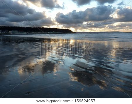 A stormy sky reflected in wet sand.