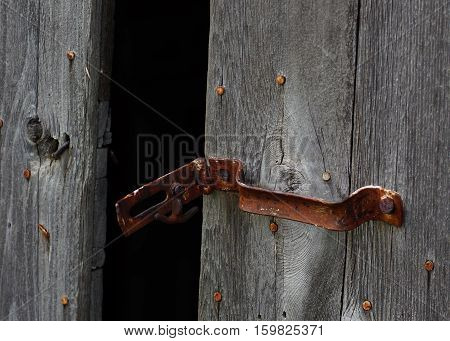Antique rusty metal barn door latch on weathered barn wood
