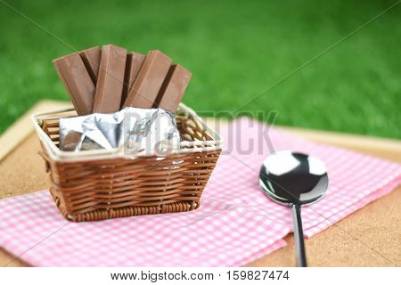 chocolate wafers and stainless steel spoon on grass in gardenselective focus.