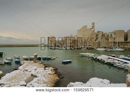 SEASCAPE WINTER.Giovinazzo's harbour.ITALY(Apulia).View of snow covered old town: on background the Cathedral of Santa Maria Assunta in Apulian Romanesque style.