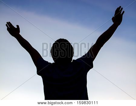 Happy Man Silhouette with Hands Up on the Sky Background