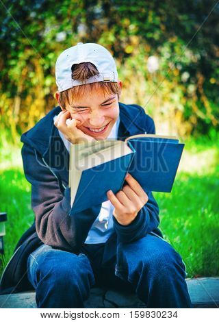 Cheerful Teenager read a Books in the Park
