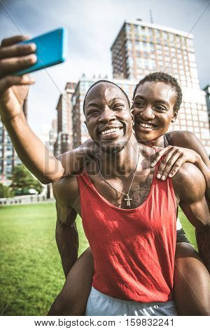 Couple running in New York - Sportive man and woman training outdoors and having fun while resting