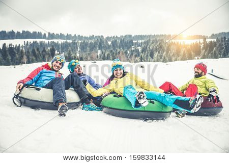 Group of friends with ski on winter holidays - Skiers riding on slides on the snow