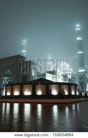 Illuminated mosque in the night fog. Religious background