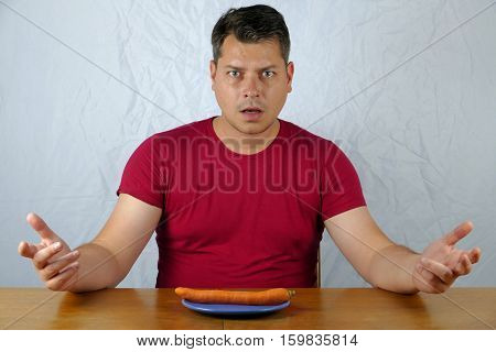 Young man dislike carrot on plate healthy food concept.