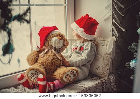 little girl in a Santa Claus hat with teddy bear sitting on the window. The child looks out the window and waiting for Christmas Santa Claus