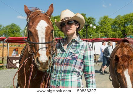 Podmitrov CZE - MAY 7 2016: Young cowgirl with hat riding a beautiful paint horse in Mitrov Czech republic