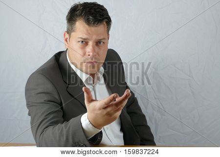Young angry business man hand mimicry on isolated background