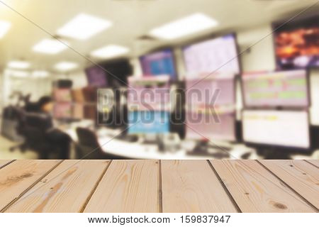 Wooden board empty table in front of blurred background of Blurring man operated plant by monitor at control room for mock up display or montage your products vintage filter.