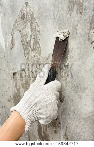 hand scraping off old wet wallpaper with spatula