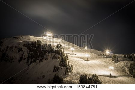 Ski slope with lights at night with misty clouds