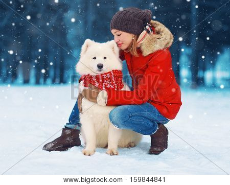 Christmas Happy Young Woman Owner Petting Embracing White Samoyed Dog On Snow In Winter Day Over Sno