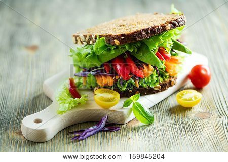 Vegan rye sandwich with fresh ingredients: avocado salad tomato carrots for healthy meal vitamin and diet food
