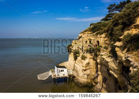 A white fishing hut next to some old walkways that cut through the cliffs