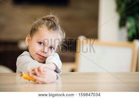 Thoughtful portrait of little girl lay on the table.