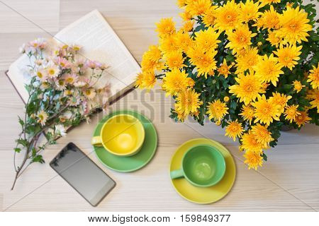 bouquet of yellow chrysanthemums on a table on a blurred background books cups and a phone. top view