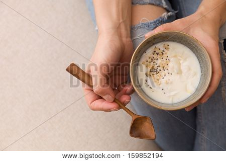 Closeup of woman's hands holding cup with organic yogurt with coconut and chia seeds. Homemade vanilla yogurt in girl's hands. Breakfast snack. Healthy eating and lifestyle concept