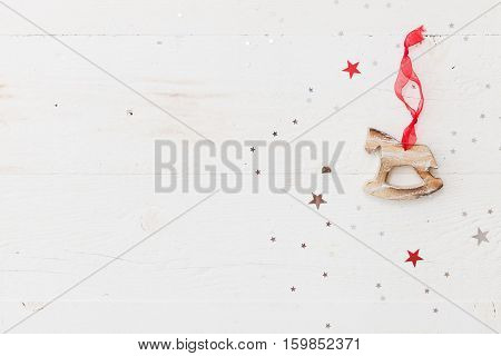 Top view on wooden horse Chrstmas decoration on retro wooden background with sparkling stars. Holiday season and celebration concept.