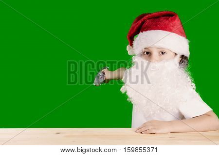 A little boy in an image of Santa Claus looking at the camera. The right arm is extended towards green background. Remote control in his hand. Finger presses the button. Сhromakey. Close-up.
