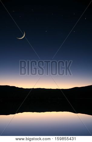 Light from the setting sun at dusk is reflected in a lake, with a crescent moon overhead.