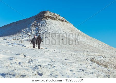 People walking on the snow in a mountain path in Wales. Man and woman wearing hi-tech clothes. Snow covering hills in the early morning. Nature and weather concepts.