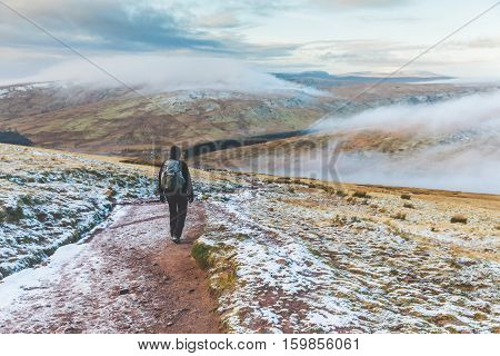 Man walking on snowy hills in Wales. Adult man hiking in winter hills covered in snow and mist on background. Wanderlust nature and exploration concepts.