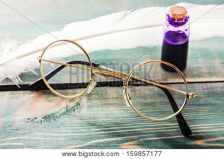 Closeup of old glasses near quill and inkstand on green wooden table.