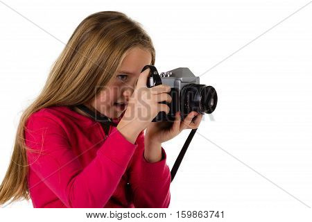 Young girl looking through the viewfinder of a vintage SLR camera isolated on a white background