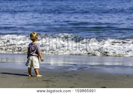 2 year old girl looking at the sea for the first time barefoot on the sand          For the first time I see the sea.