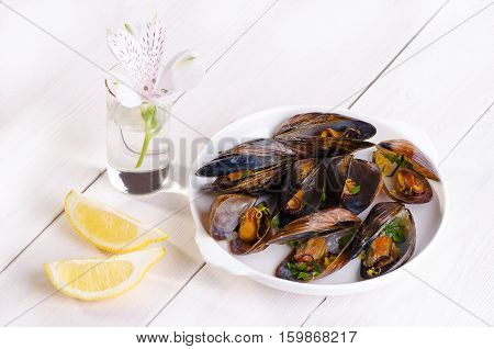 Mussels in a white plate with parsley and lemon zest