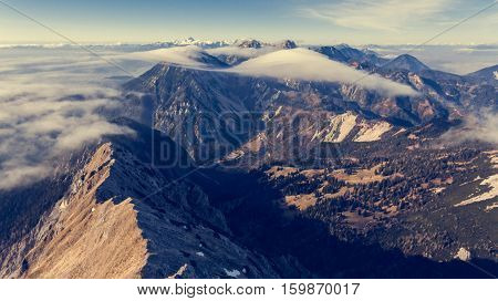 Aerial view above mountain ridge with river of clouds. Karavanke in Slovenia.