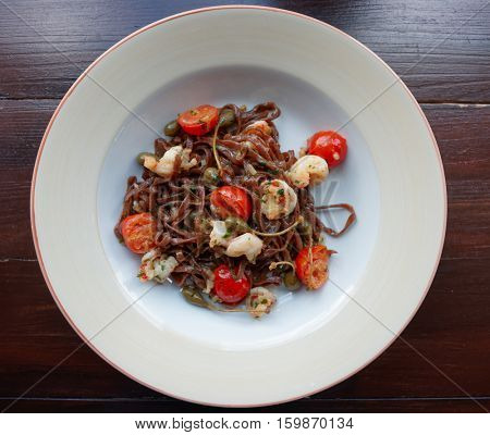 Rye pasta with capers and prawns shot from above