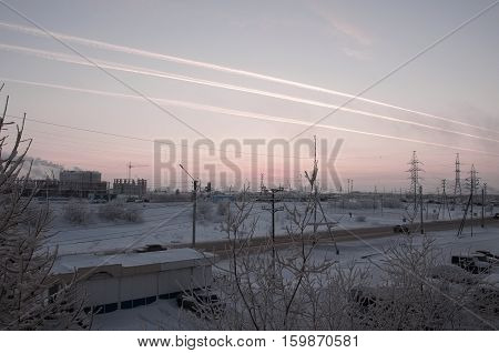Pink sunset on the winter industrial street with prints in the sky after the airplane  View from window in the cold frosty evening. Road with cars