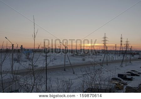 Orange sunset on the winter industrial street. View from window in the frosty evening. Road with cars