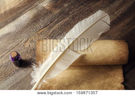 Writing concept. Closeup of scroll and quill near inkstand on wooden table.