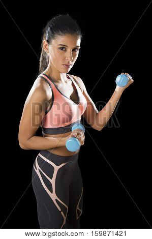 young attractive latin sport woman posing in fierce and badass face expression holding dumbbell hand weight isolated on black background in healthy lifestyle and fitness concept