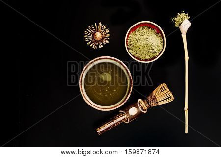 Chasen - special bamboo whisk, spoon for matcha tea and beverage with apetite foam. Black background. Photo made in flat lay style. Focus is on matcha foam.