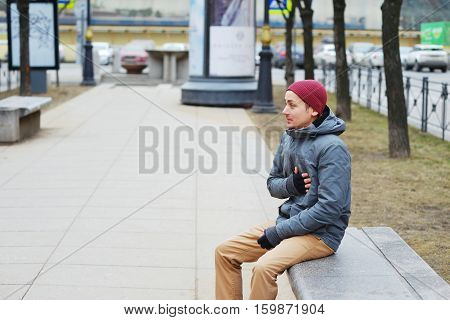 Young tired man sits on a bench in the alley and keeps a hand on the heart.