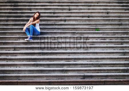 The pensive long-haired young girl in t-shirt and jeans sits alone on a stone staircase her eyes downcast.