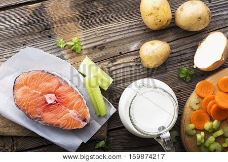 piece of fresh sea northern salmon on a wooden background with vegetables before cooking