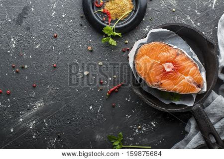 Portion magnificent sea wild northern salmon before cooking with spices and salt on a dark background in the form of cast iron.