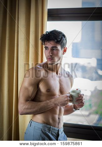Sexy handsome young man standing shirtless in his bedroom next to window curtains, holding a coffee cup