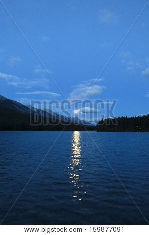 Moonrise with clouds over a lake. Banff, Canada.