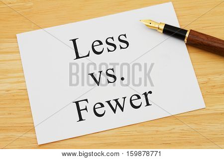 Learning to use proper grammar A white card on a desk with a pen with words Less vs Fewer