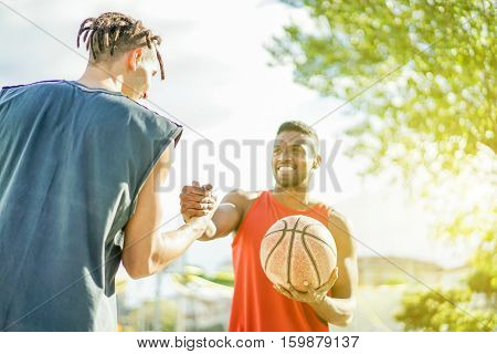 Baskeball players shakings hand before two on two game - Multiracial basket athletes showing respect clapping hand - Fair competition against racism concept - Focus on hand - Warm filter with sunlight