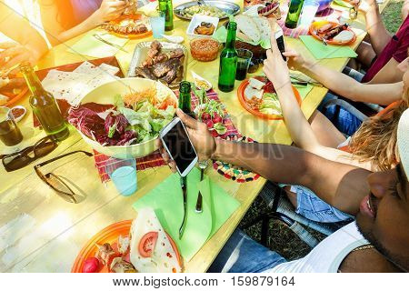 Happy friends laughing and using mobile phones during barbecue lunch outdoor - Young people socializing at bbq party with beers and grilled meat - Focus on right phone bottom hand - Warm filter