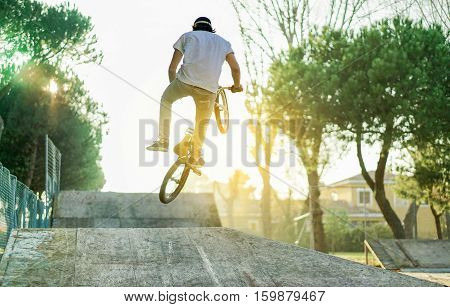 Biker jumping in bmx pro jump session outdoor in city urban park with back light - Young man making extreme sport at sunset - Danger activity concept - Soft focus on man head silhouette - Warm filter